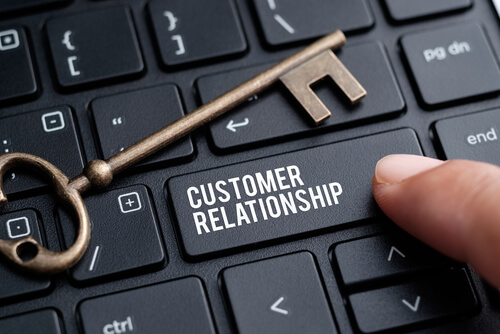 Closeup of finger on keyboard with words CUSTOMER RELATIONSHIP